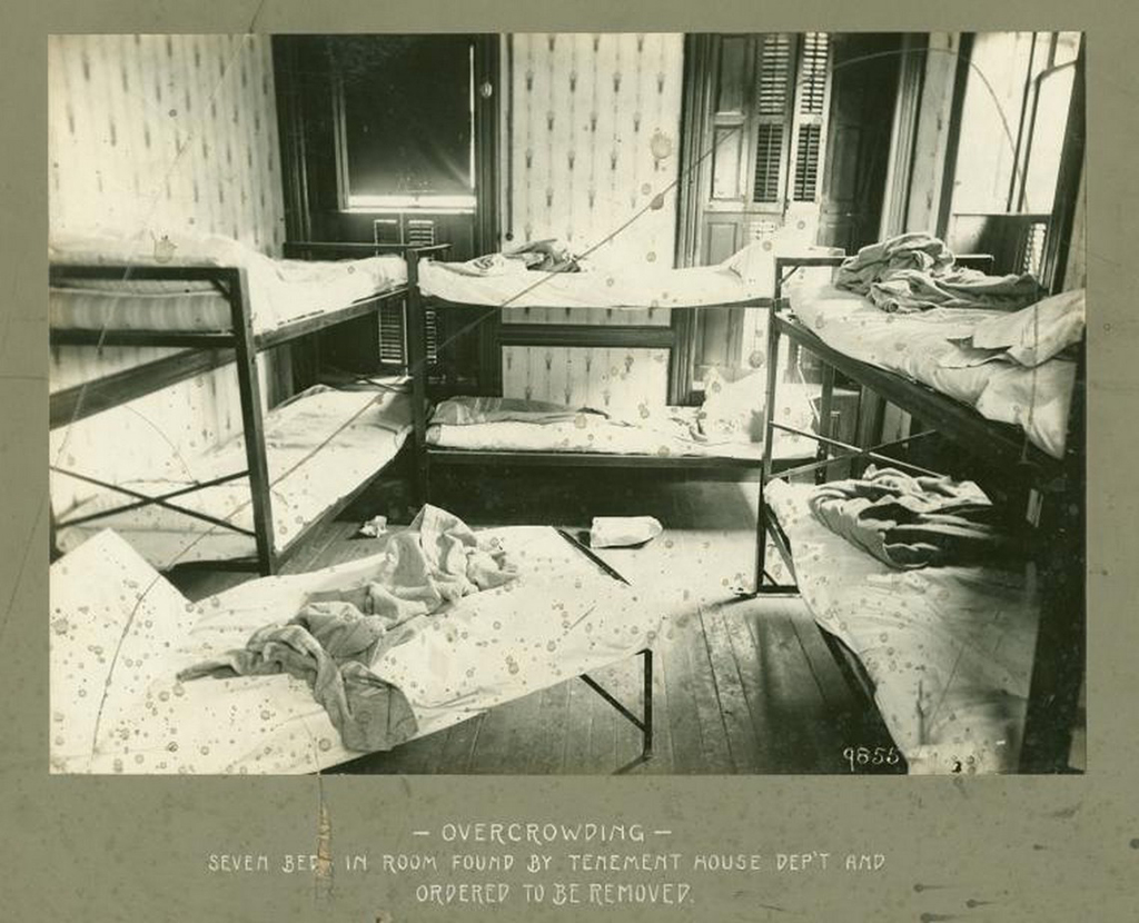 "Photo of a tenement room in 1902 taken during an inspection by the New York City Tenement House Department | Photo via <a href=""https://digitalcollections.nypl.org/items/510d47e3-4ca2-a3d9-e040-e00a18064a99"">NYPL</a>"