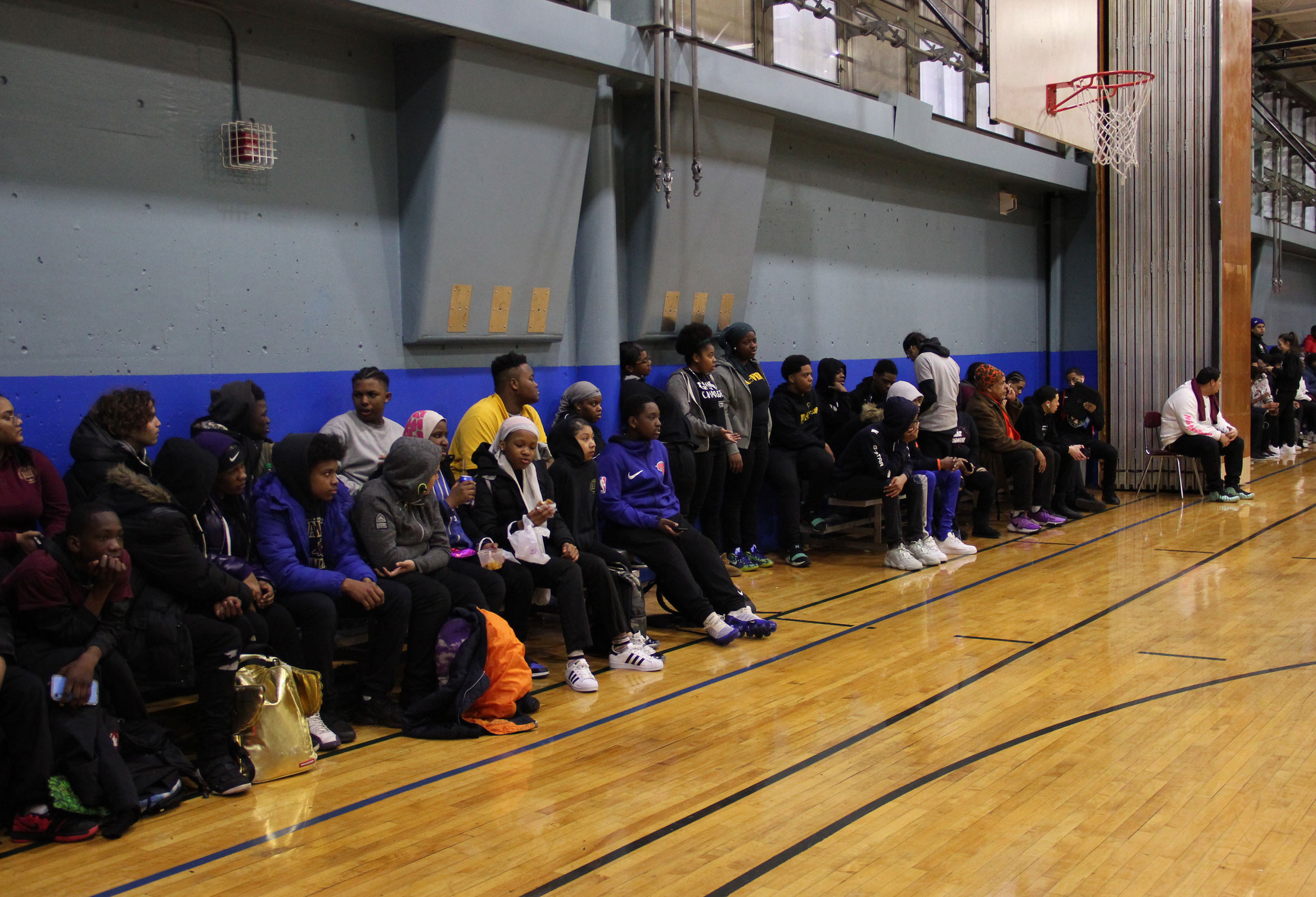 Spectators crowd the sidelines in the Bronx Letters gym. A partition divides the space to allow multiple physical education classes to run simultaneously. Photo by Olivia Schwob