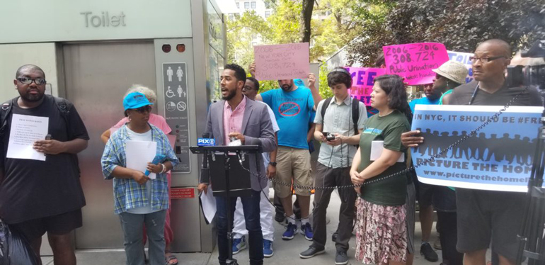 "A ""Free To Pee"" protest and press conference next to an automatic public toilet in Madison Square Park. Image via <a href="" https://picturethehomeless.org/"">  Picture the Homeless</a>"